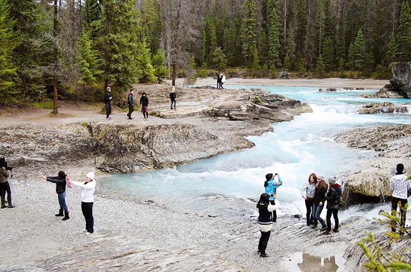 Tourists take selfies along a creek